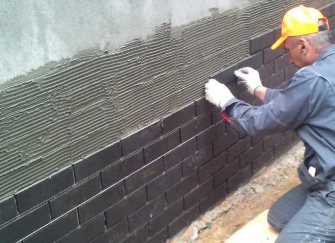 Рабочий крепит фасадную плитку