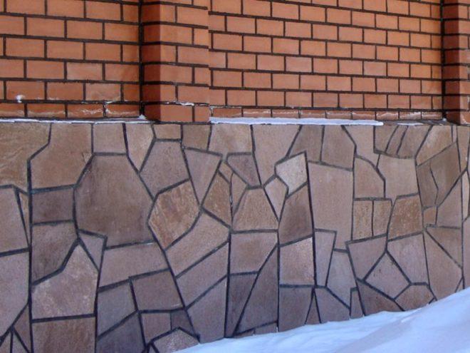 Фундамент дома, отделанный камнем