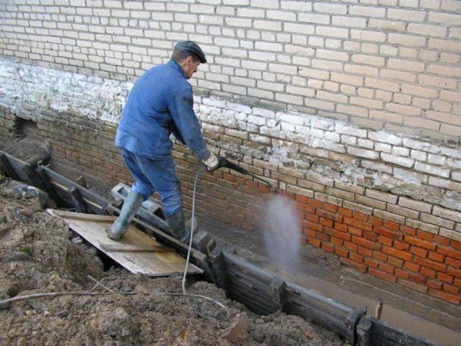 Рабочий очищает фундамент водой