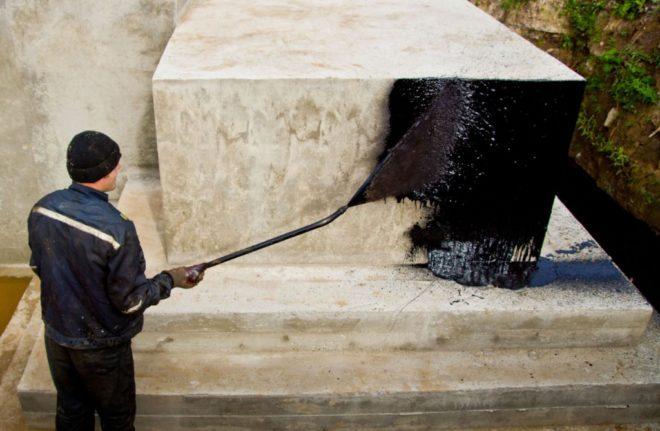 Рабочий наносит слой гидроизоляции распылителем