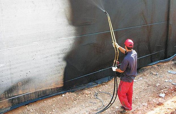 Рабочий распыляет жидкую резину
