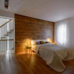 Комната с деревянной отделкой в изголовье кровати