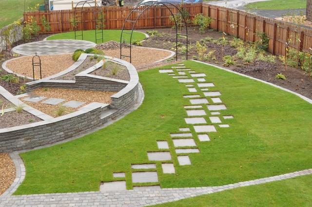 ландшафтный дизайн двора частного дома с дорожкой, выложенной камнями