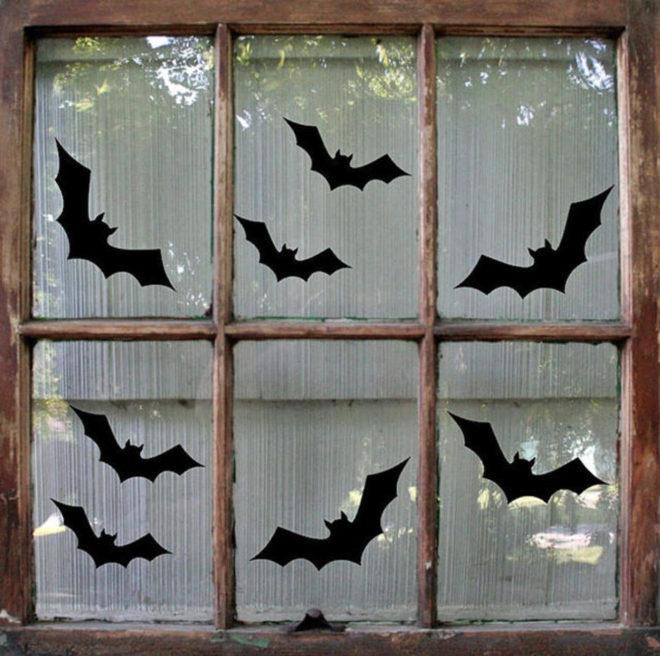 Летучие мыши из чёрной бумаги украшают окно на Хэллоуин