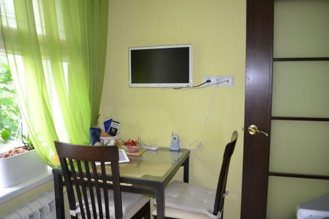 Вариант размещения телевизора над обеденным столом на кухне