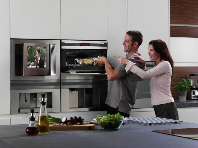 Молодая пара на кухне со встроенной техникой