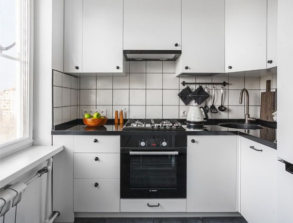 Белая угловая кухня с раковиной в углу между плитой и холодильником