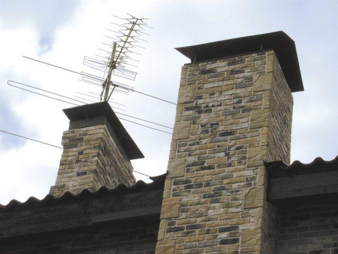 Кирпичный дымоход над крышей