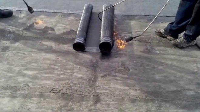 Рабочий укладывает наплавляемый материал