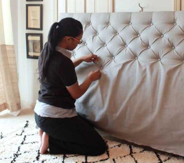 Девушка украшает старый диван