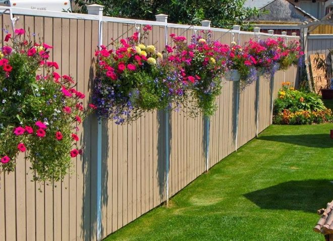 Цветы в горшках на заборе
