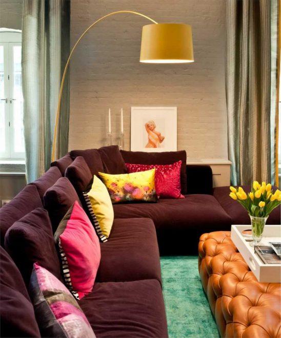 Бордовая софа с яркими подушками и ламповое кресло