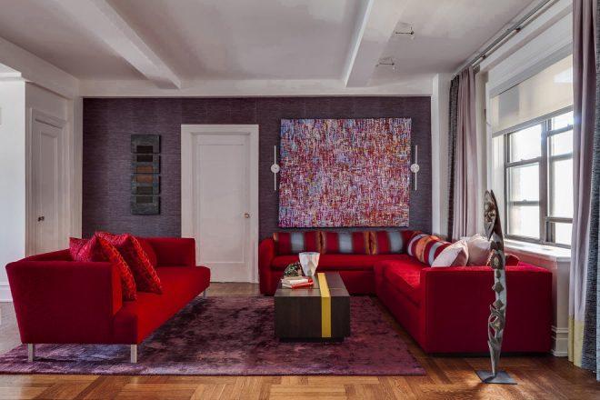 Ярко-красные диваны с подушками на нейтральном фоне