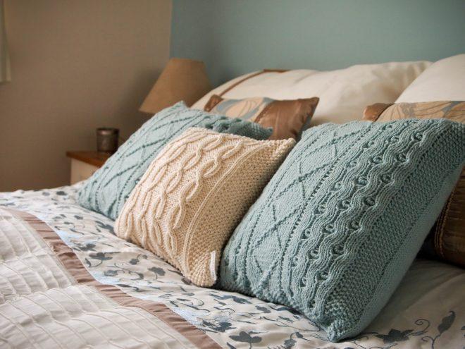 Вязаные подушки на двуспальной кровати